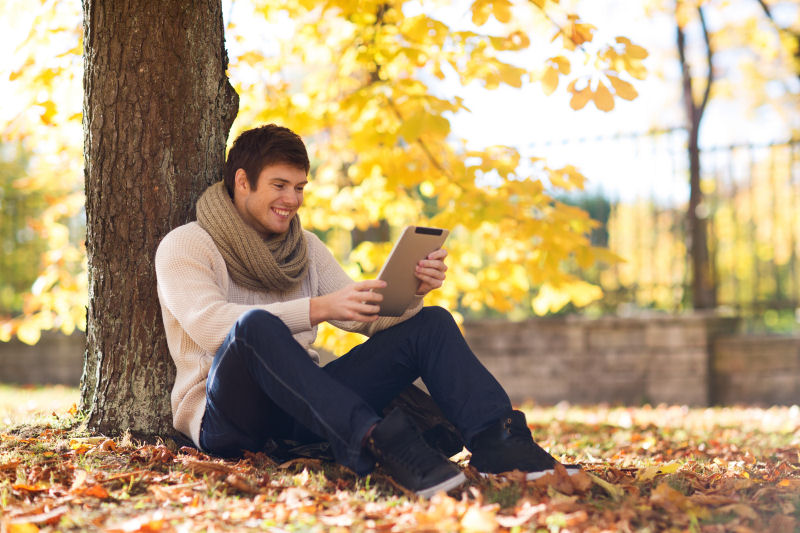 9620381-smiling-young-man-with-tablet-pc-in-autumn-park800